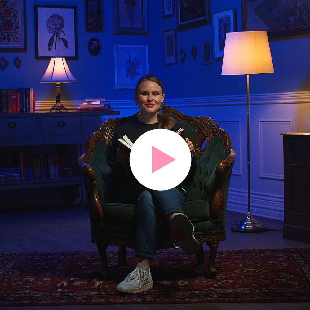 Léa Clermont-Dion est assise sur un divan avec un livre.