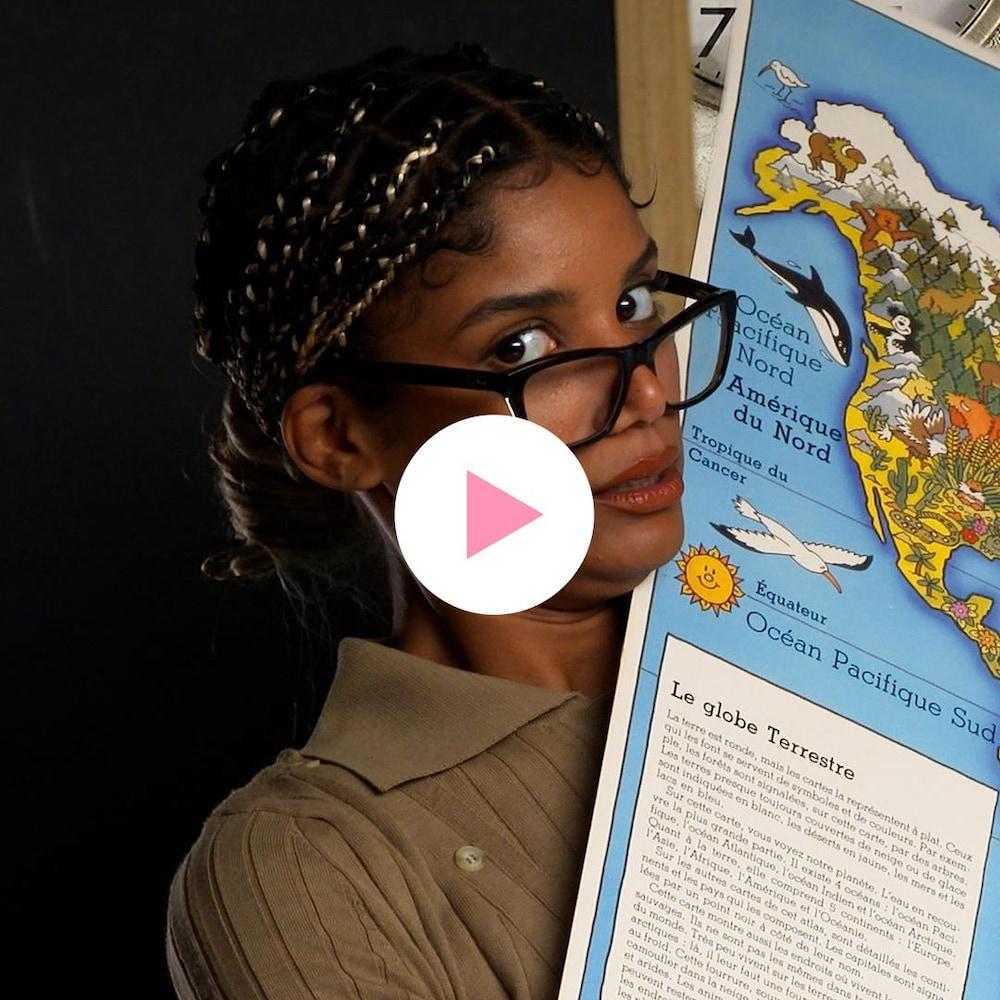 Audrey Roger est vêtue comme une enseignante et tient une carte du monde.