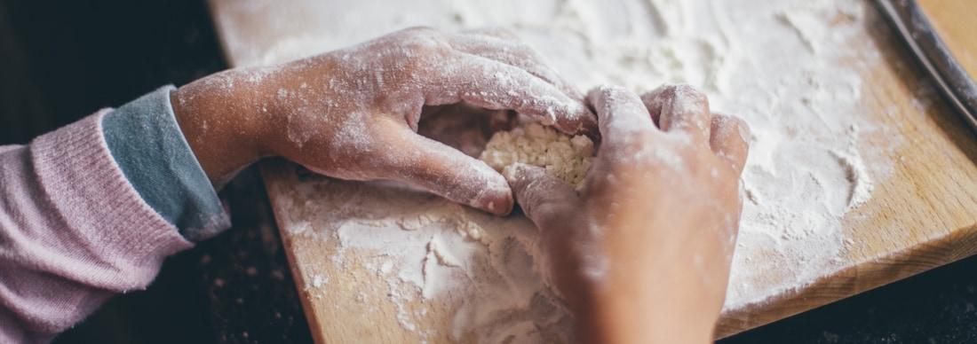 Gros plan sur de petites mains pleines de farine.