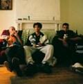 Image de la série web «Dominos» mettant en scène les trois personnages principaux, assis - ou plutôt avachis - sur un sofa. De gauche à droite: Fred (interprété par Émile Schneider), Toto (interprété par Greg Beaudin, aka Snail Kid dans les Dead Obies) et Adib (interprété par Benjamin Roy).