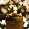 Un cadeau doré devant un sapin illuminé