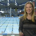 Photo de la chroniqueuse Geneviève Tardif devant la piscine olympique de l'Institut national du sport du Québec.