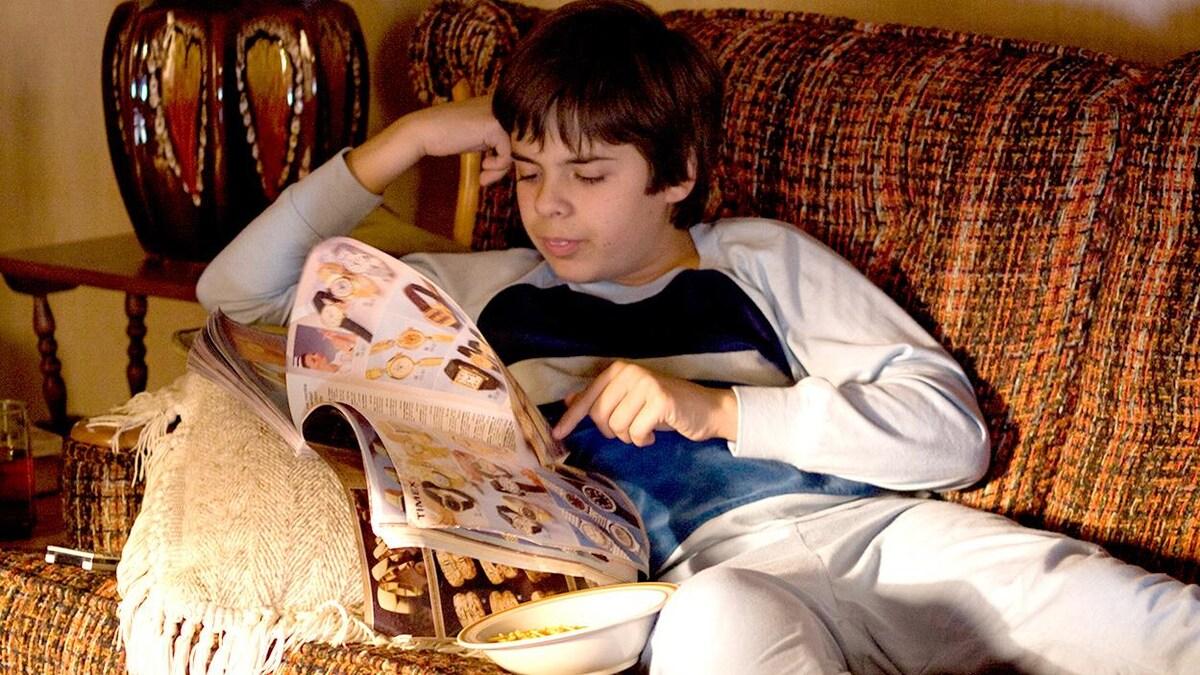 Un garçon en pyjama, sur un sofa, lit un catalogue.