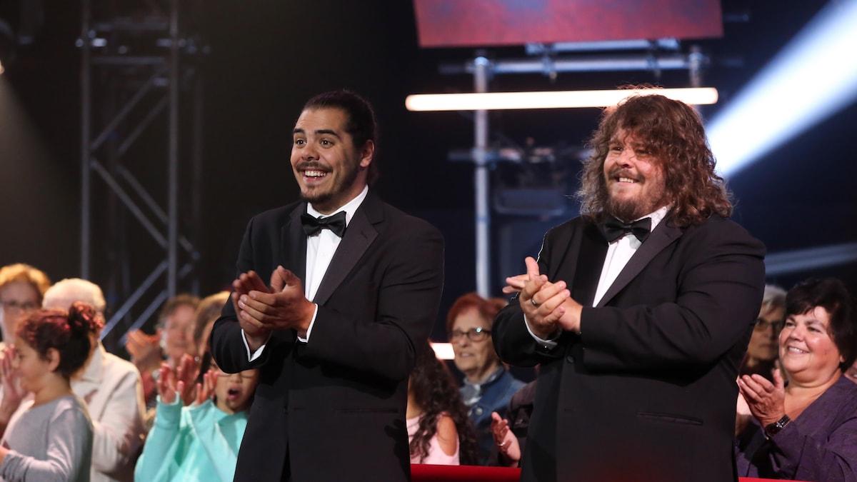 Deux hommes en tuxedos applaudissent.