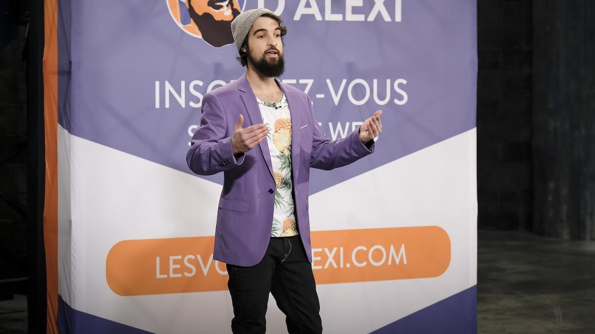 Alexi porte un jeans, un t-shirt à motifs d'ananas et un veston lilas.