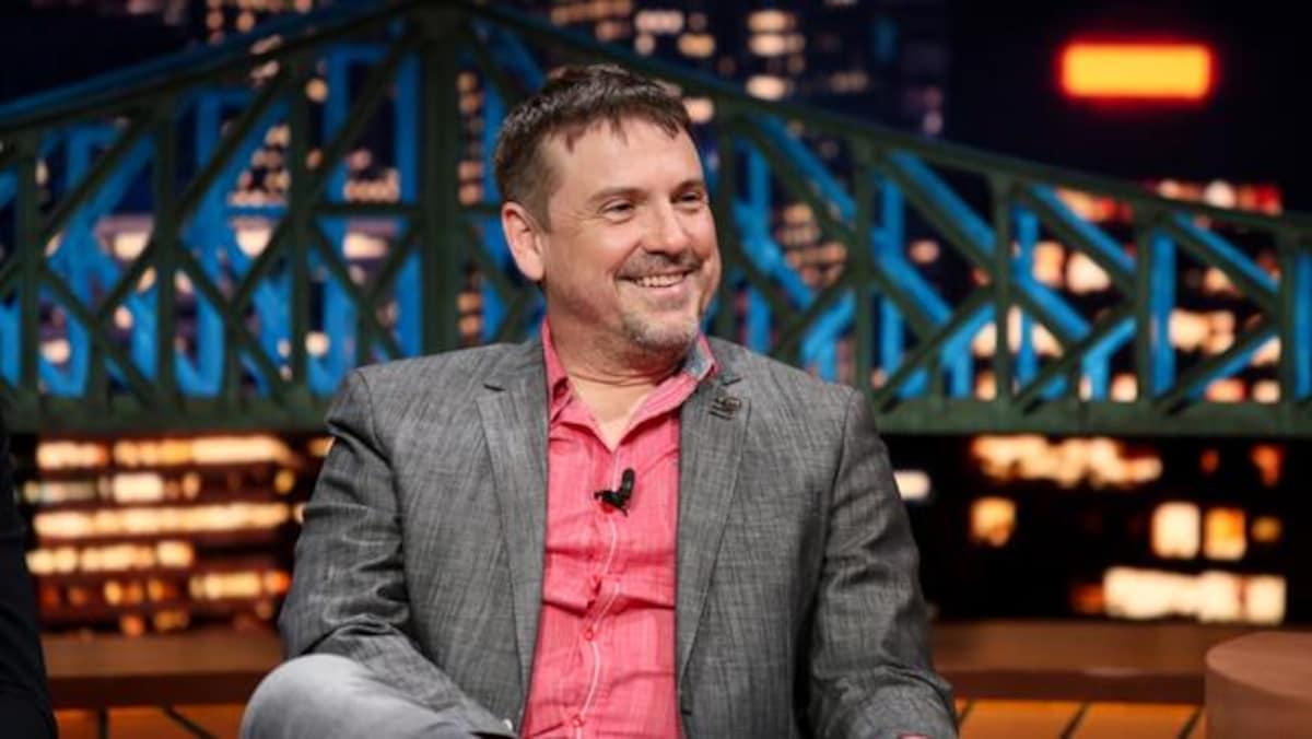 Dans le studio de l'émission  Le beau dimanche , Claude Legault, vêtu d'une chemise rose et d'un complet gris, sourit.