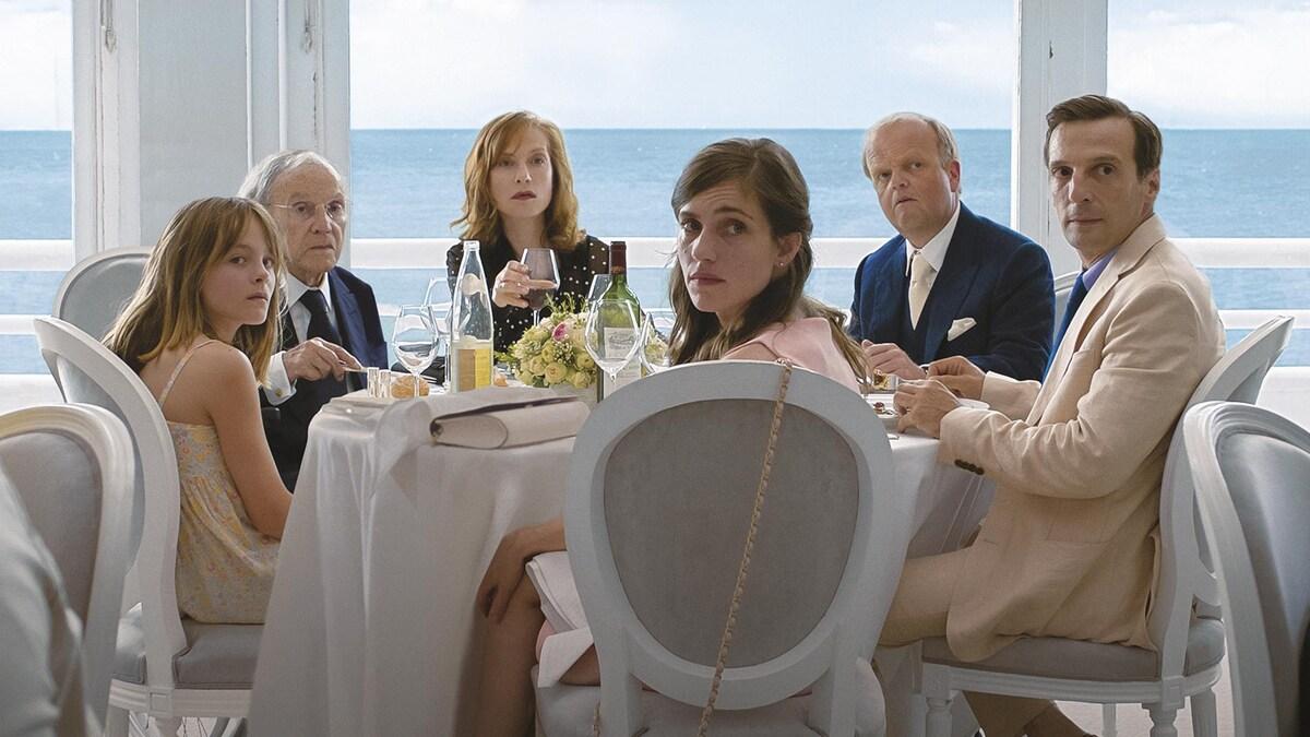 Une famille assise autour d'une table blanche, devant une fenêtre donnant sur la mer