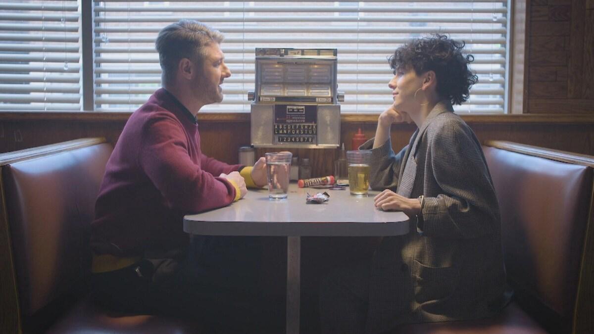 Les deux artistes sont face à face sur une banquette d'un restaurant.