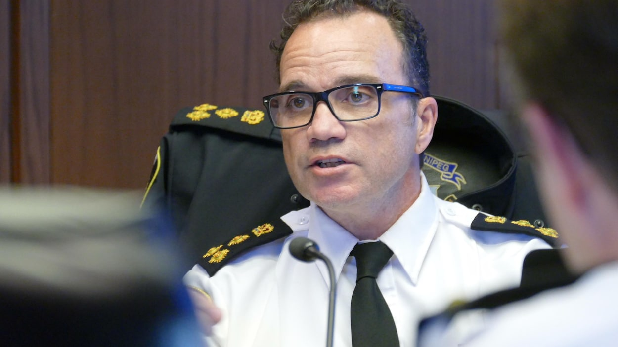 Gros plan sur le haut du coprs du chef de la police, Danny Smyth. Il parle à des collègues. Il est en uniforme.