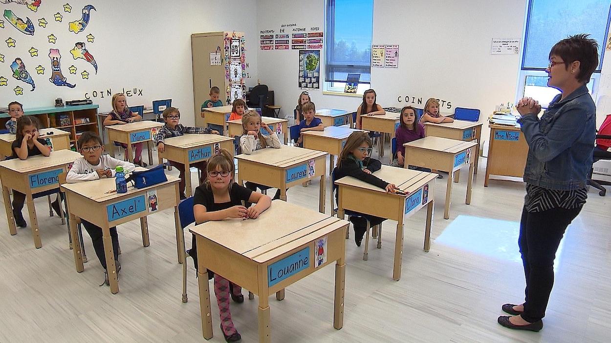 Quinze élèves écoutent leur professeur.