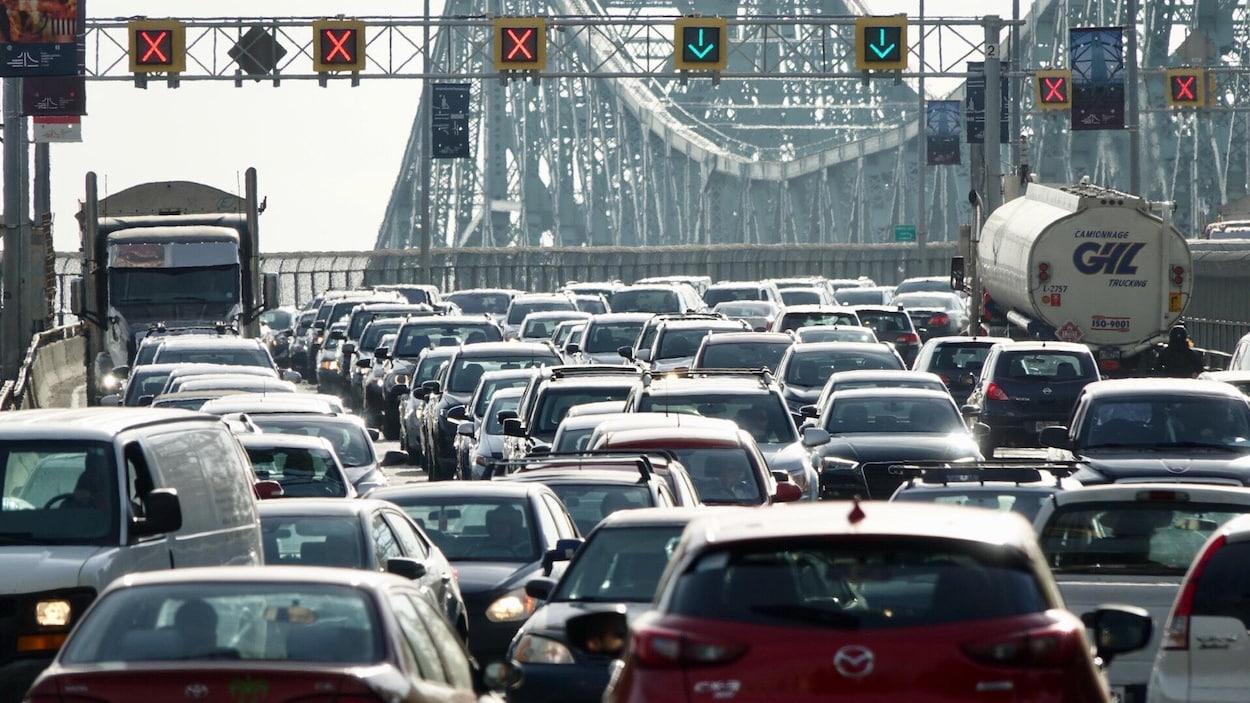 Plusieurs véhicules sont pris dans la congestion routière du pont Jacques-Cartier, à l'heure de pointe matinale à Montréal, alors qu'on voit les feux de circulation signalant les voies ouvertes et fermées dans les deux sens.