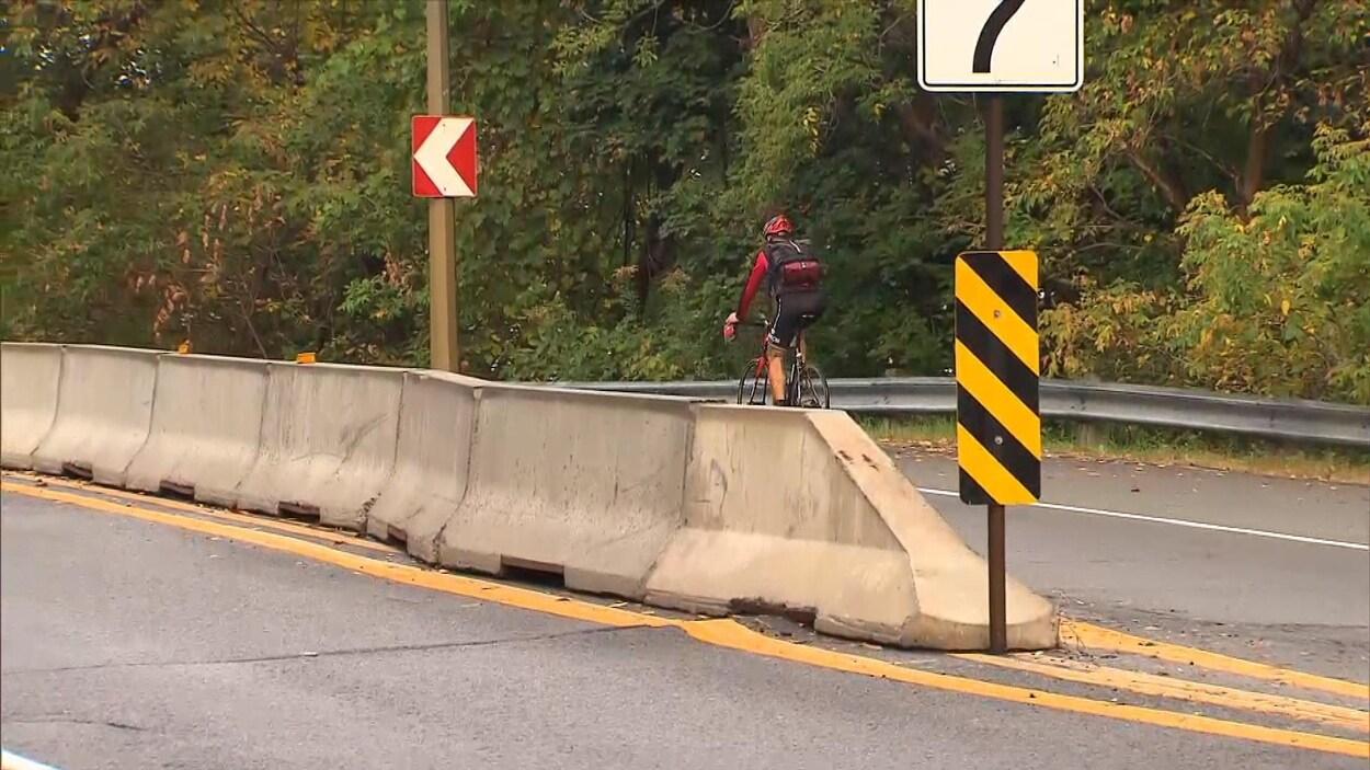 Un cycliste sur une portion de la voie Camillien-Houde séparée par des murets, sur le mont Royal