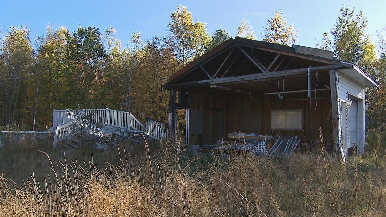 Maison entourée de bois dont la façade est manquante à cause de l'incendie.