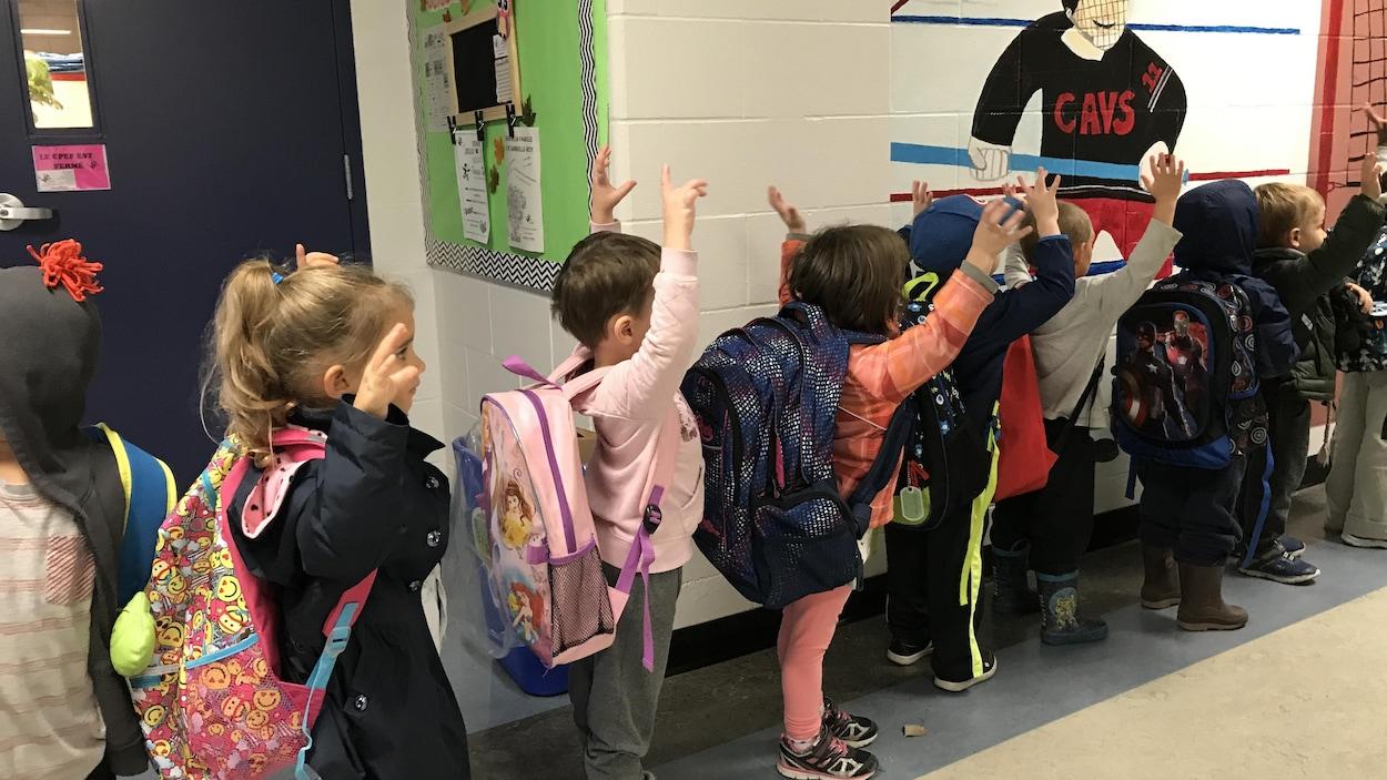 Des enfants font la file. Ils ont leur sac à dos et ils sont prêts à quitter leur classe.