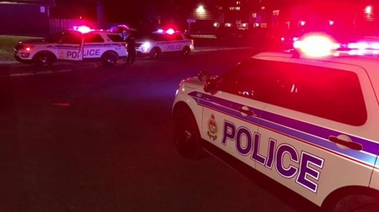 Trois voitures de police devant un immeuble à logement.