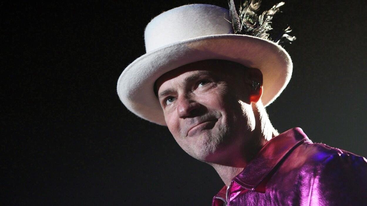 Le chanteur Gord Downie sourit en levant les yeux au ciel, son chapeau blanc sur la tête.