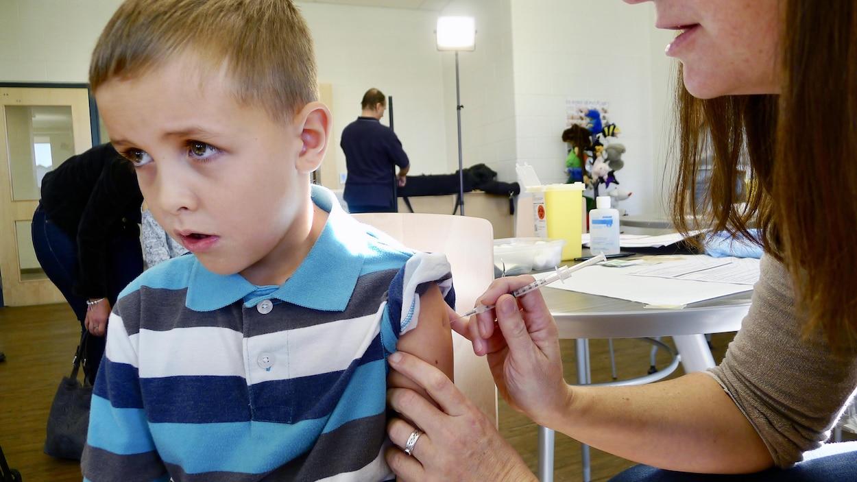 Un enfant se fait vacciner contre la grippe.