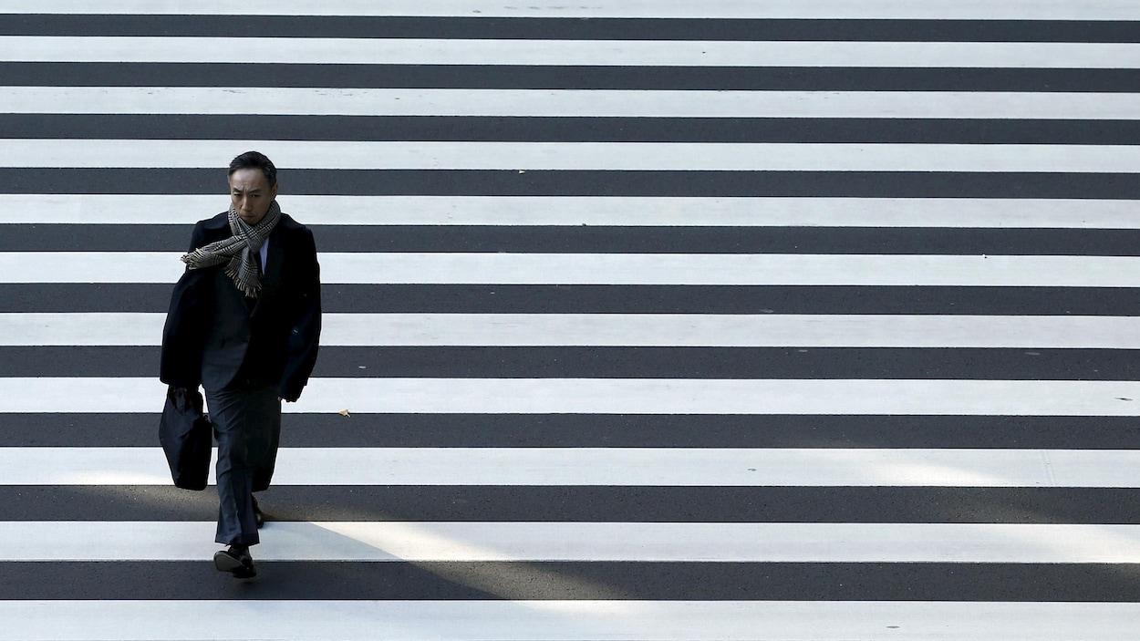 Un homme d'affaires traverse une rue à Tokyo.