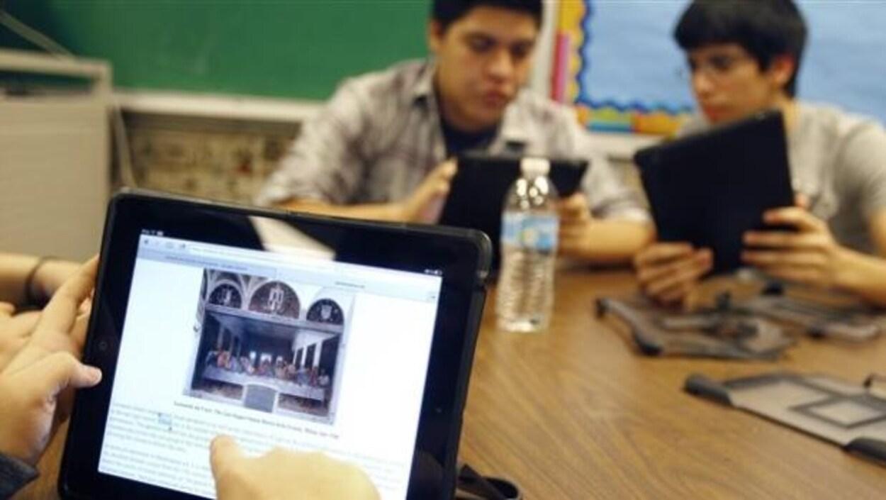 Des élèves travaillent sur des tablettes électroniques.
