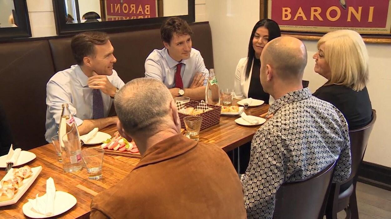 MM. Trudea et Morneau dans une restaurant avec d'autres personnes