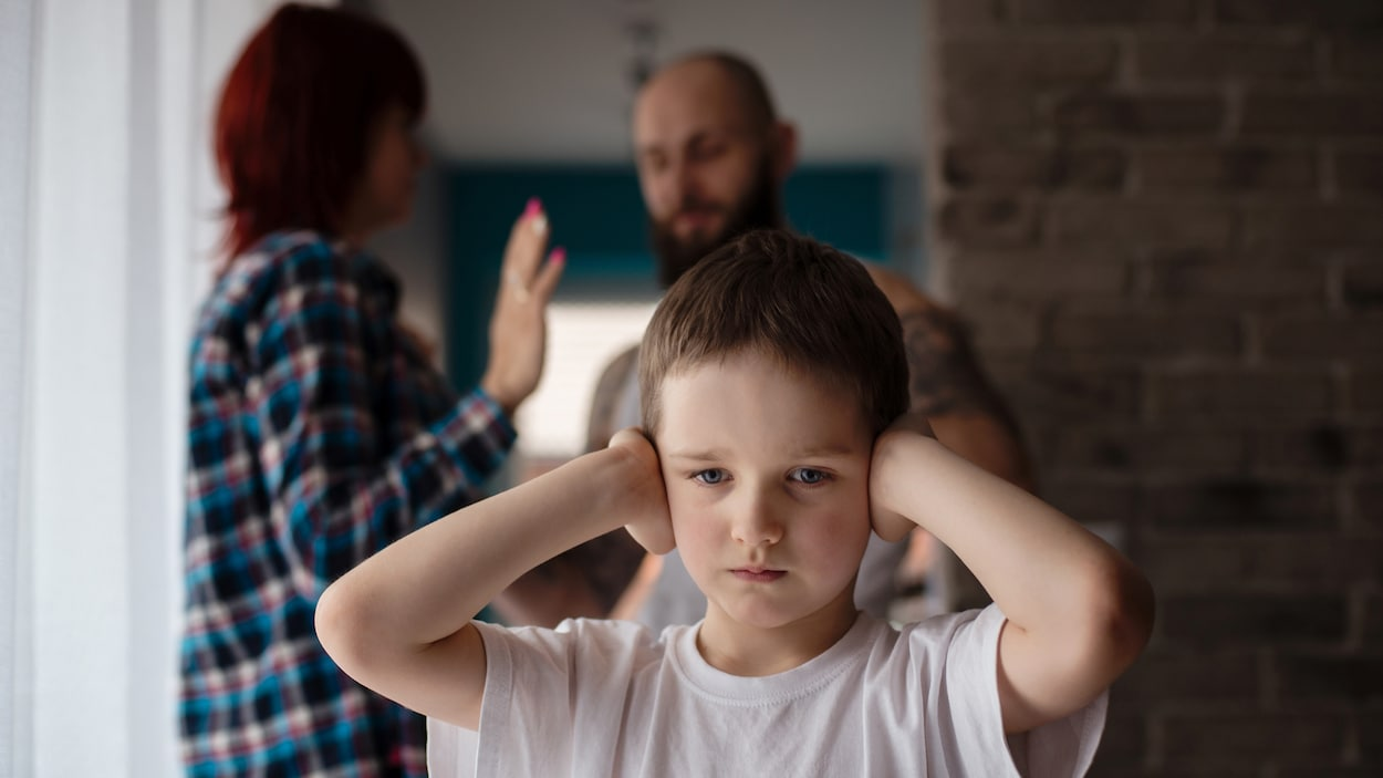 Un enfant se bouche les oreilles pendant que des adultes se disputent derrière lui.