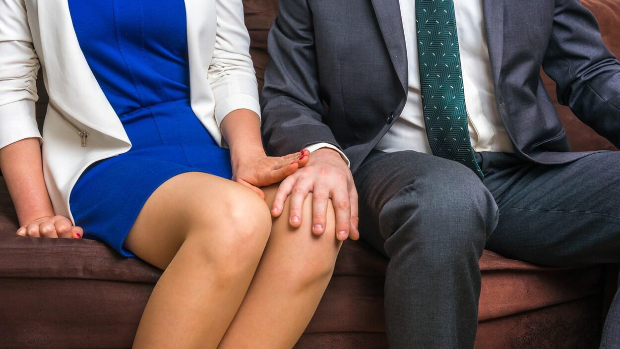 Une femme repousse la main d'un collègue qui lui touche la jambe.