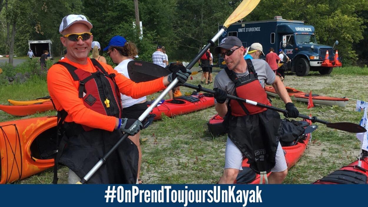 Deux hommes portant des vestes de sauvetage, des casquettes, des lunettes fumées et des jupettes de kayak, font semblant de se battre avec les pagaies en guise d'épée. Derrière, on voit d'autres kayakistes, des kayaks sur le sol et un véhicule d'urgence.