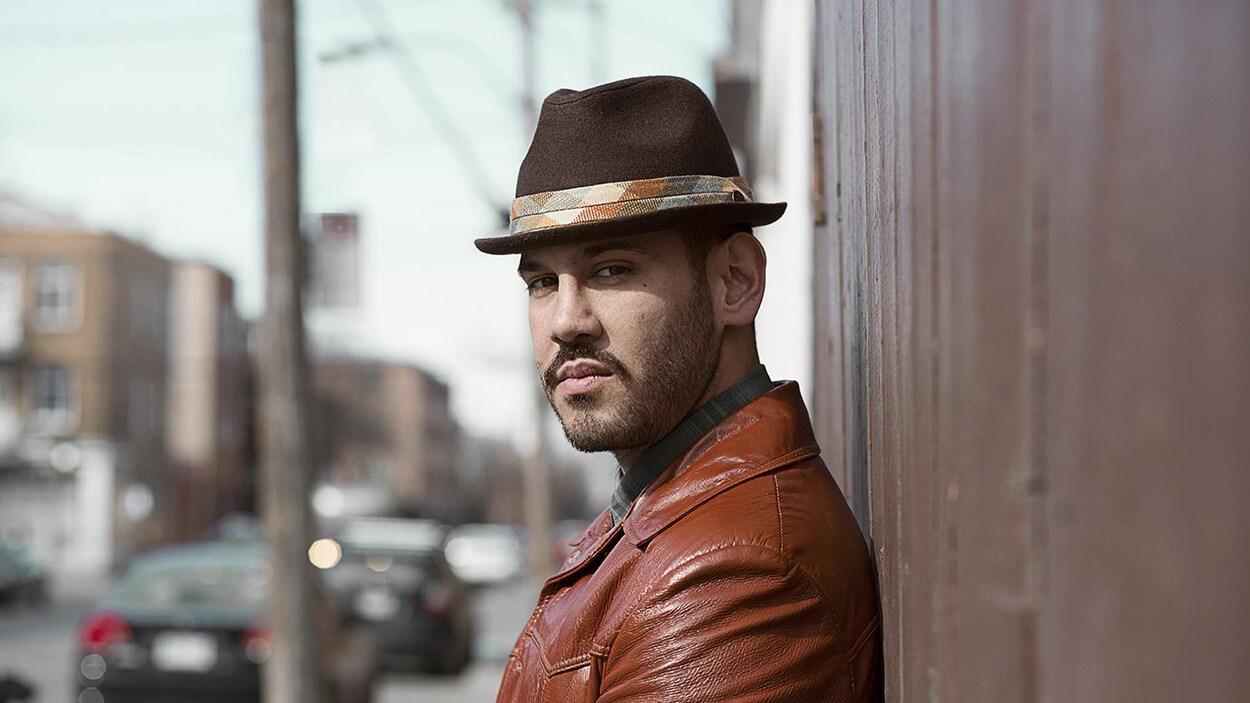 Le chanteur québécois Boogat regarde la caméra sur le côté, adossé à un mur, dans une rue.