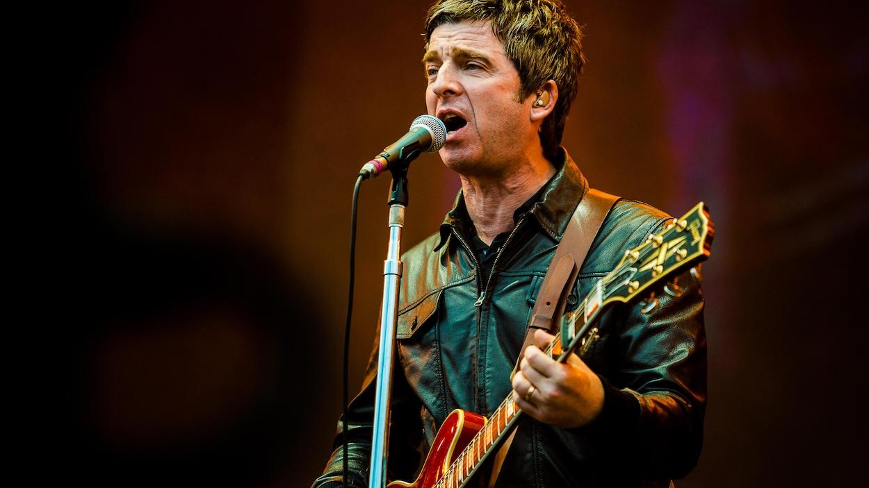 Noel Gallagher chante et joue de la guitare sur scène