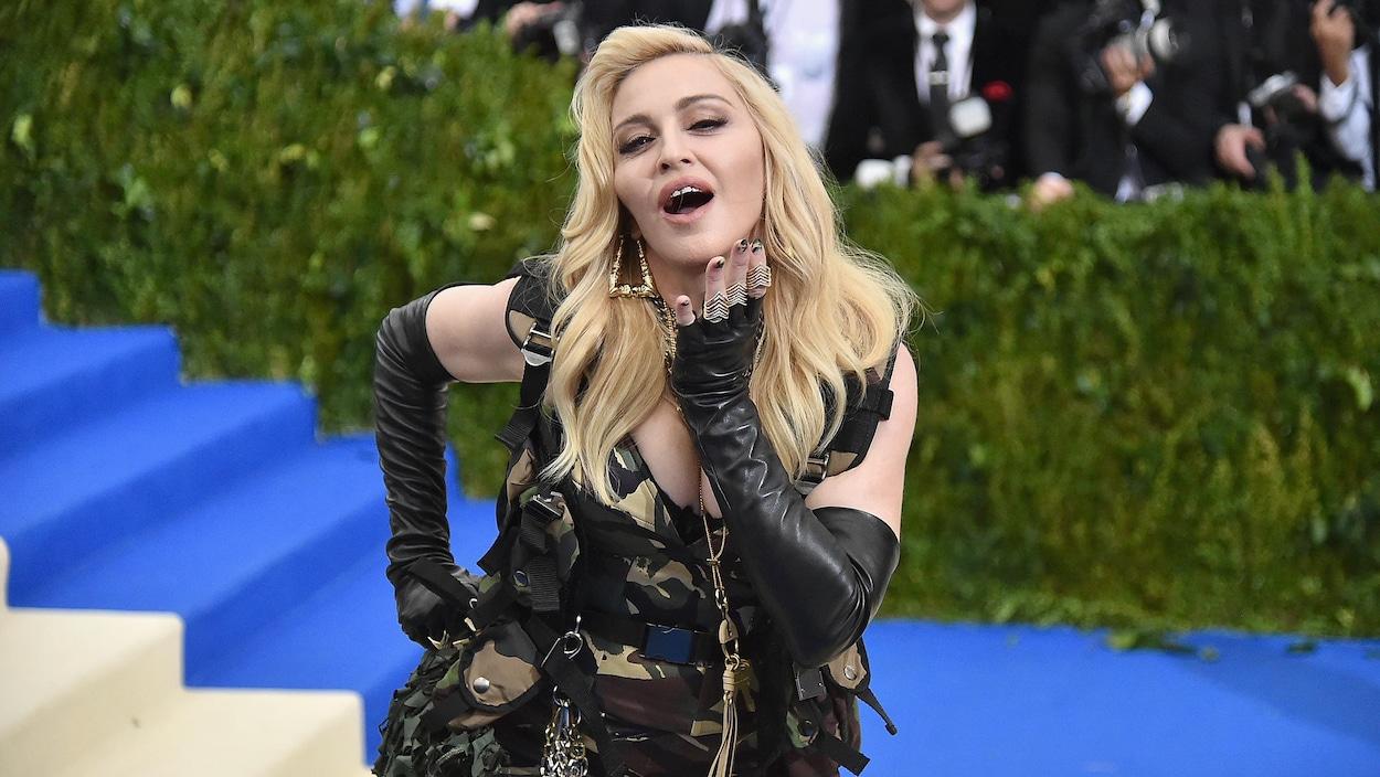 Le bras sur sa hanche, la chanteuse Madonna se penche et ouvre la bouche devant les photographes.