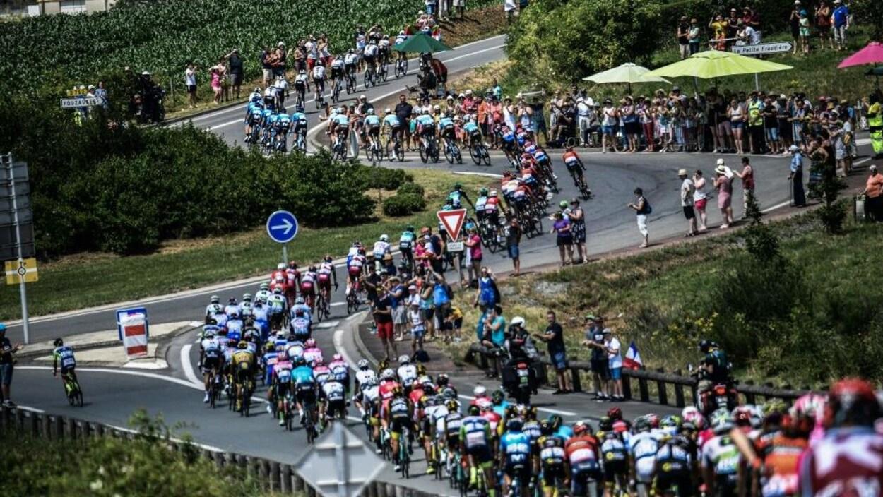 Le peloton des cyclistes négocie des virages durant le Tour de France.