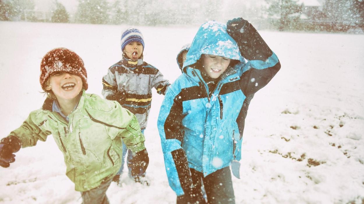 Des enfants rient en s'amusant dans la neige.