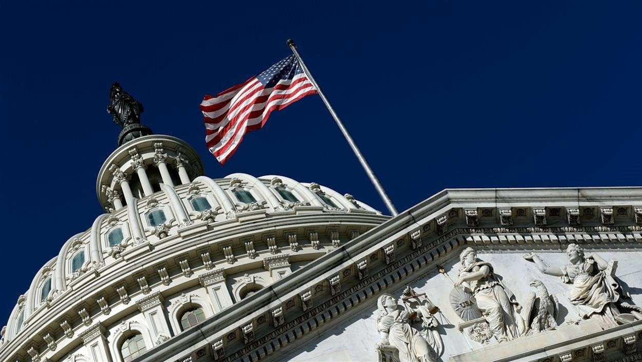 Gros plan du dôme du Capitole, avec un drapeau américain