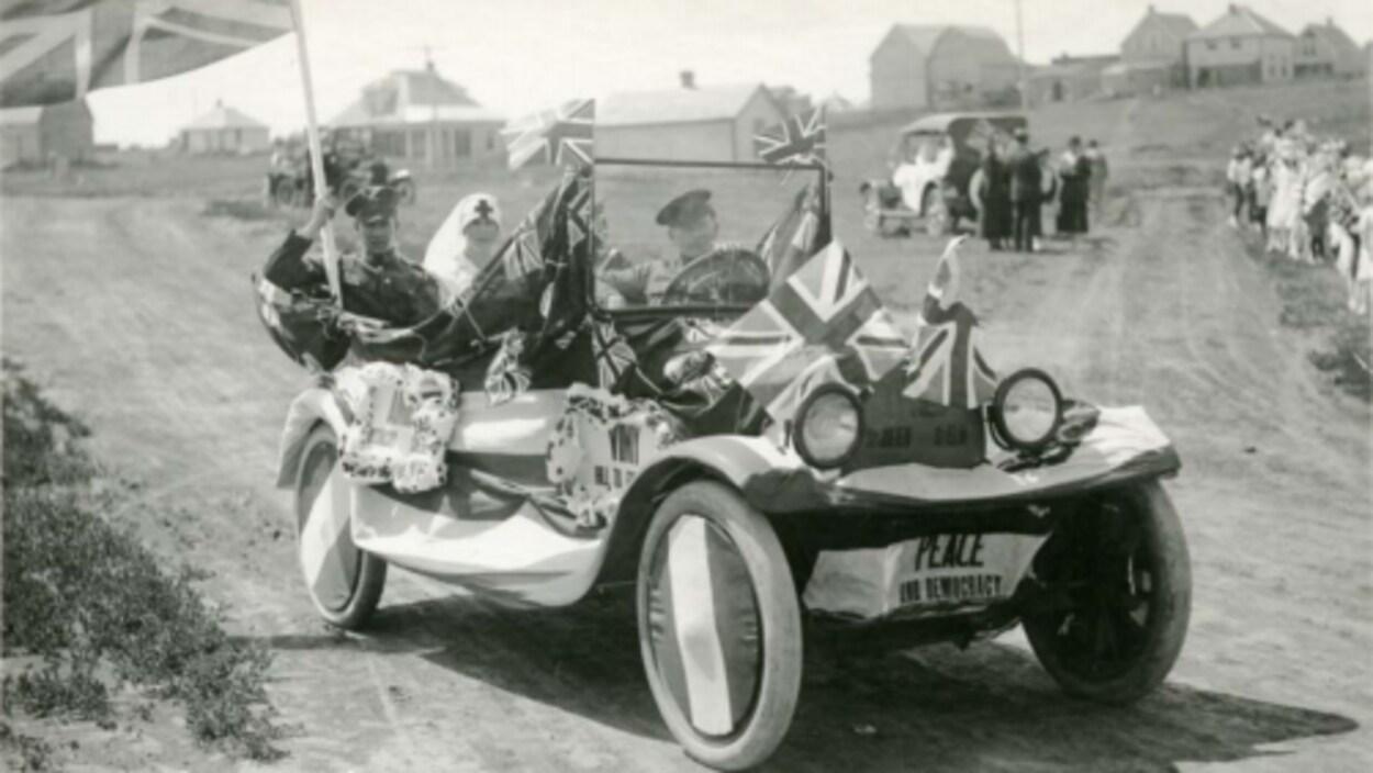 Une vieille voiture d'antan sans toit (1919) avec des soldats et une infirmière à l'intérieur et des drapeaux partout sur la voiture. C'est écrit ''paix'' devant la voiture.