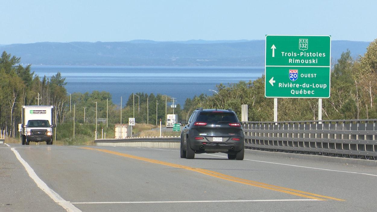 Des véhicules circulent près d'affiches de signalisation de la route 132 et de l'autoroute 20.