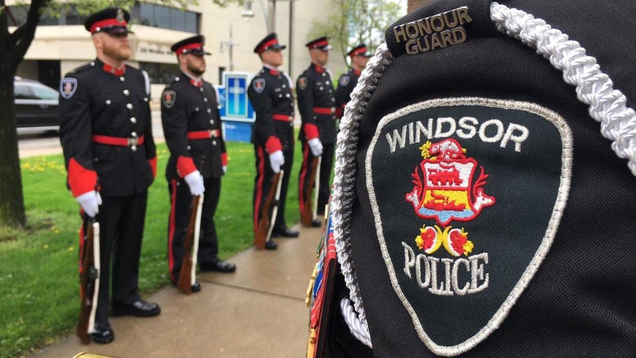 Des policiers en uniforme d'apparât lors d'une cérémonie. Au premier plan, l'épaule d'un agent montre l'écusson de la police de Windsor.