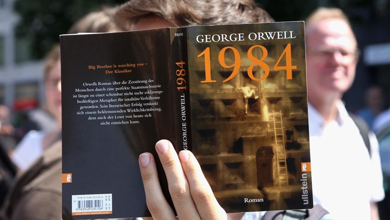 Un manifestant allemand présente un exemplaire de 1984, de George Orwell