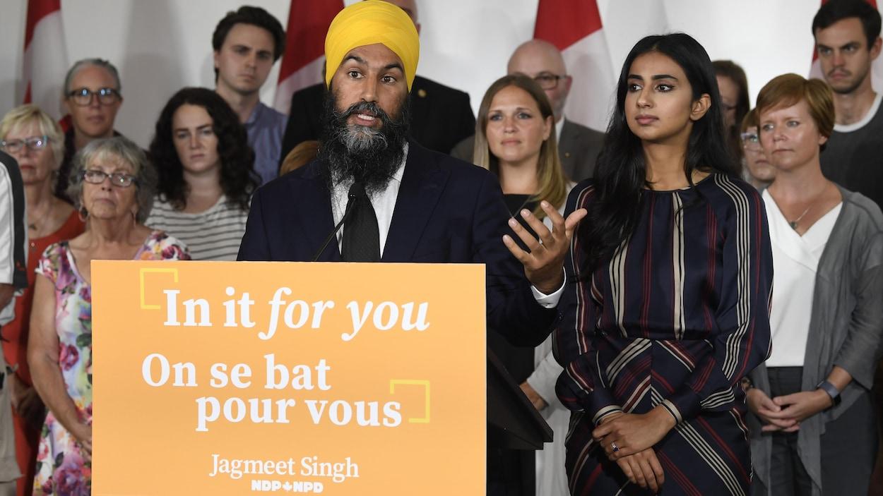 Jagmeet Singh devant un lutrin aux couleurs de son parti, avec une femme à ses côtés et des gens en arrière.