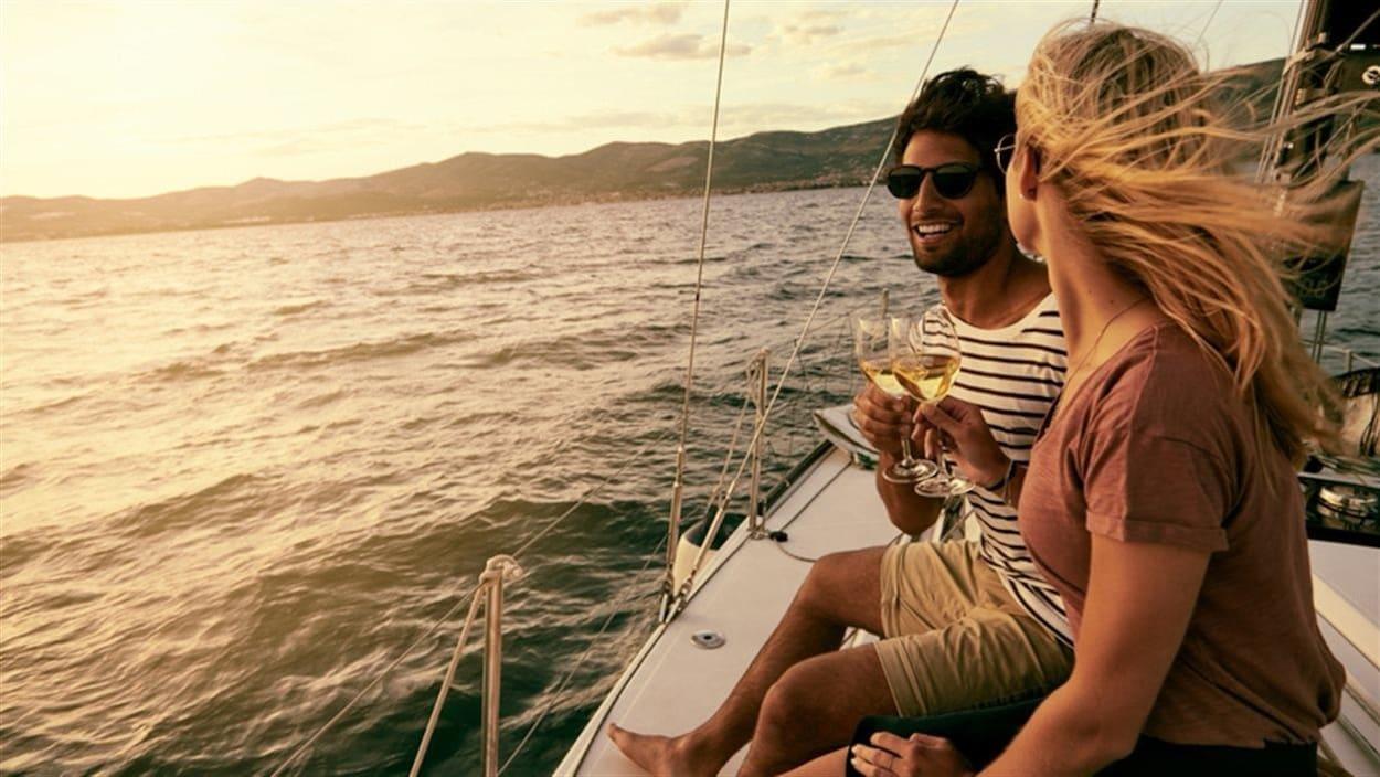 Un jeune couple prend un verre de vin sur un bateau de plaisance à la tombée du jour