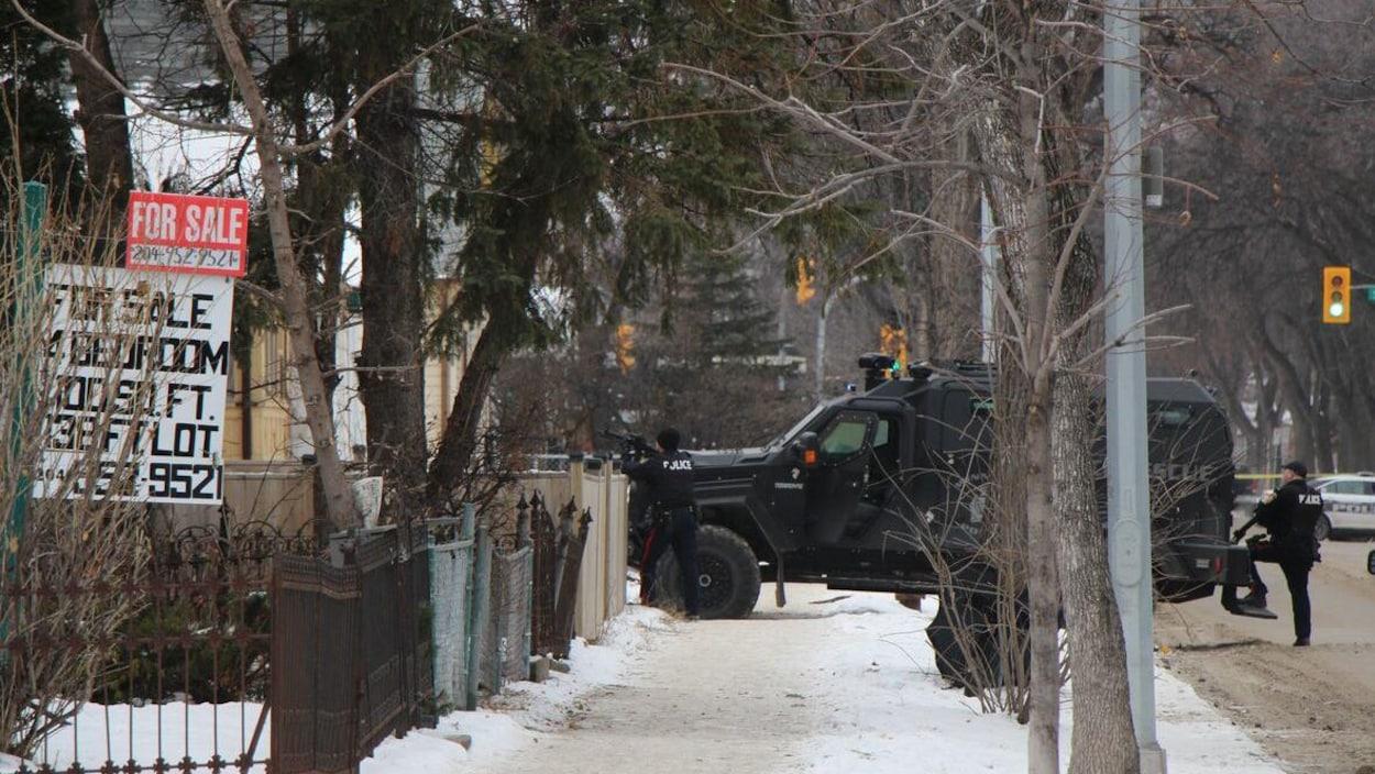 Un véhicule blindé et des policiers devant une maison.