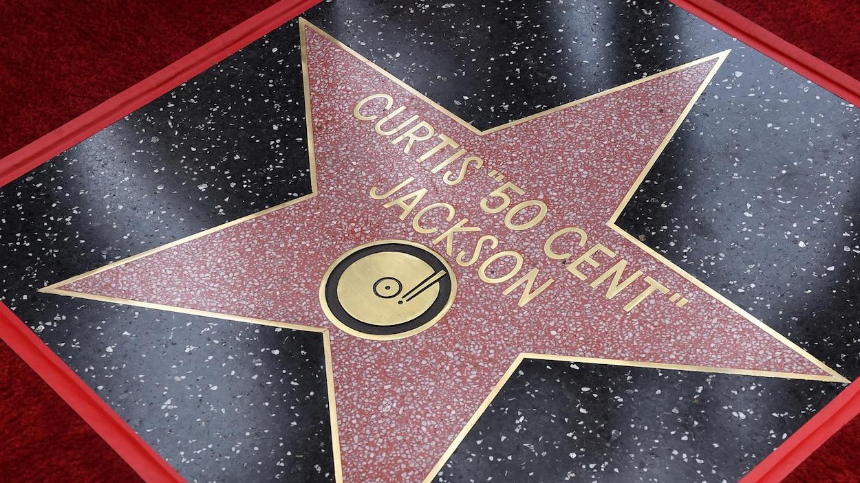 """Une tuile sur le sol où il est écrit en lettres dorées dans une étoile «Curtis """"50 Cent"""" Jackson», accompagné du symbole d'un tourne-disque."""