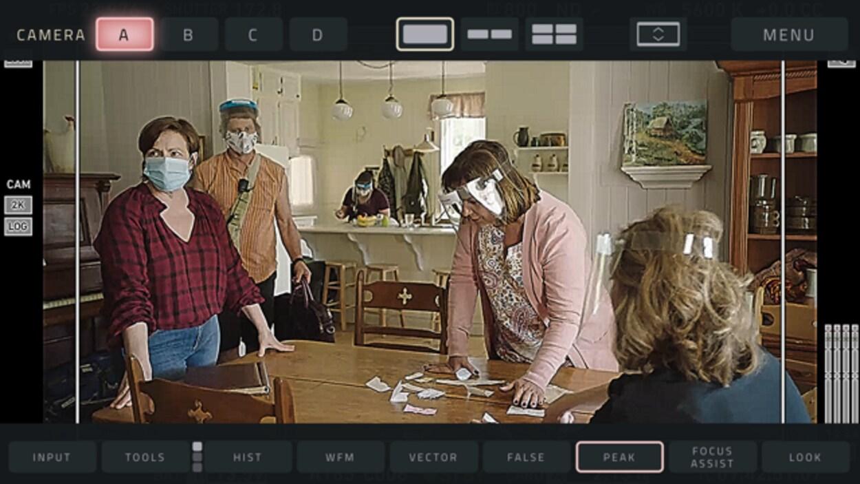 Quatre personnes masquées sont autour d'une table.