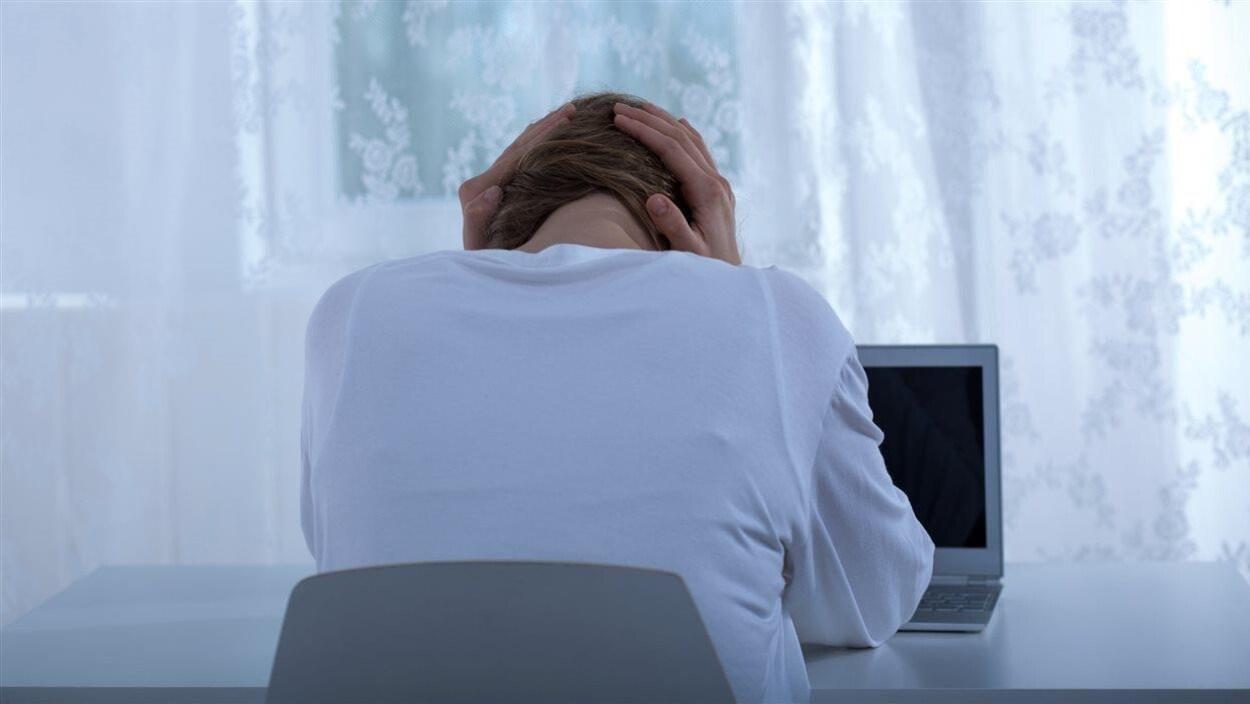 Femme se prend la tête devant un ordinateur