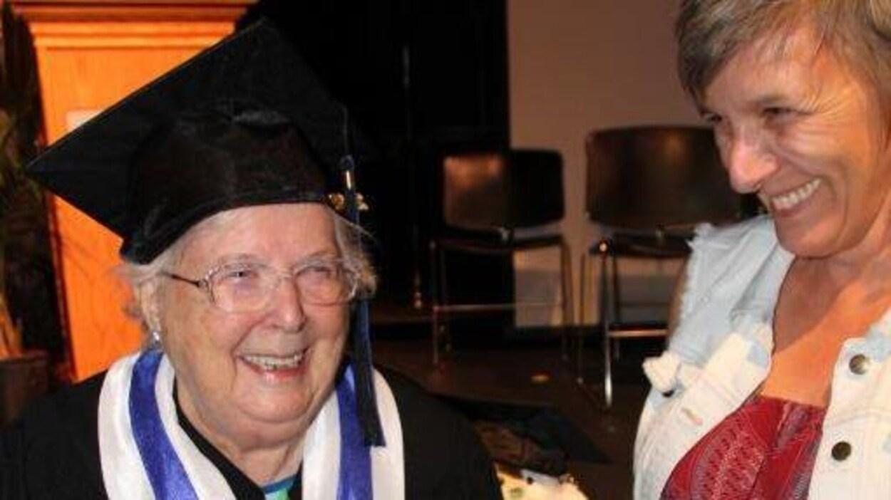 Une femme âgée habillée en toge tient son diplôme à côté d'une de ses enseignantes.