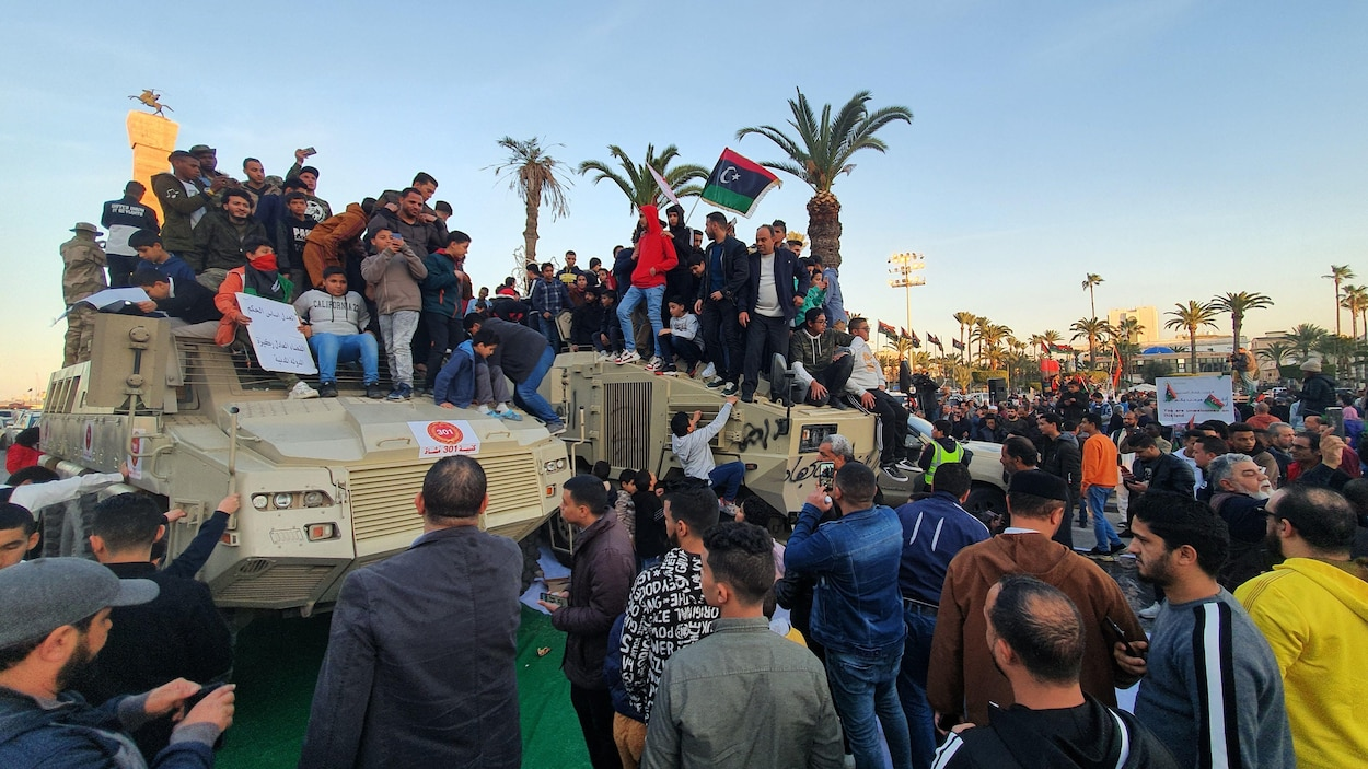 Des hommes et des enfants juchés sur des chars d'assaut agitent des drapeaux libyens dans les rues de Tripoli.