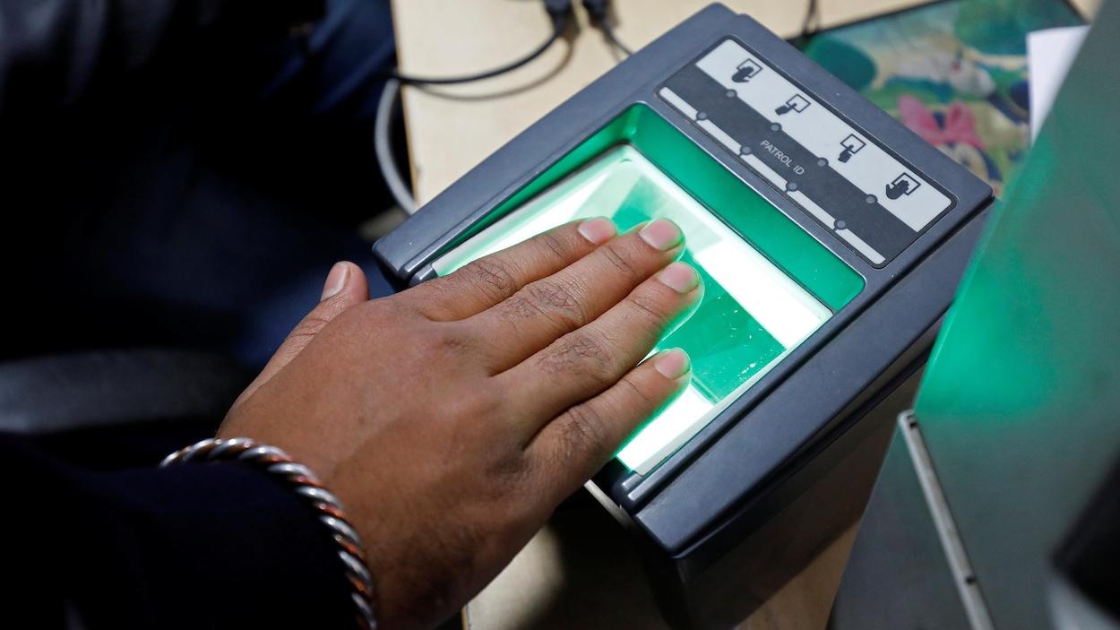 Une main de femme posée sur un appareil permettant de lire les empreintes digitales.
