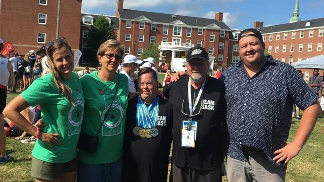 Un jeune homme homme avec quatre médailles au cou est entouré de deux femmes sur sa droite et de deux hommes sur sa gauche. Tous regardent l'objectif en souriant.