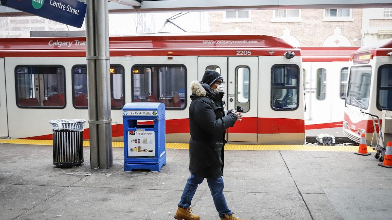 Un homme portant un masque marche sur un quai du C-Train de Calgary pendant la pandémie de COVID-19.