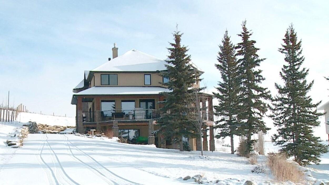 Une grande maison sur un promontoire enneigé, entourée de quelques arbres.