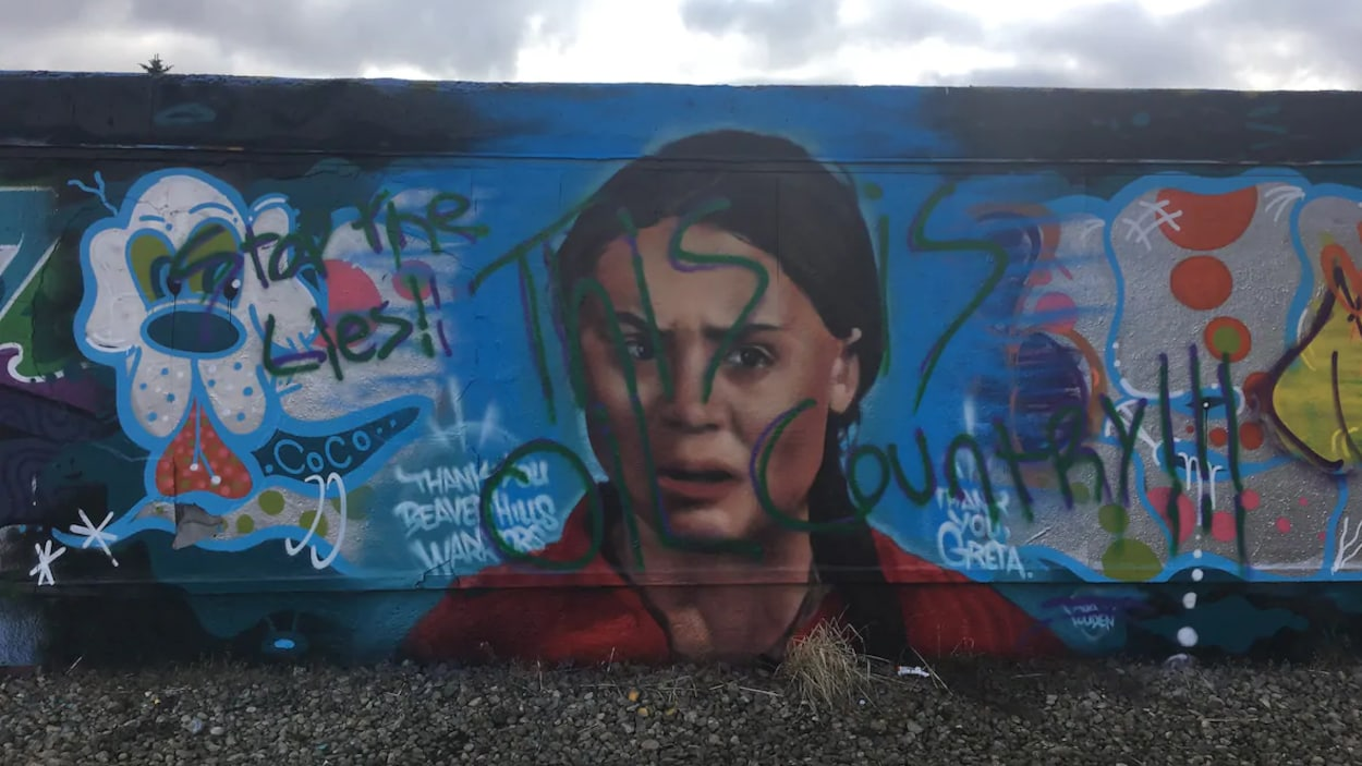Une murale colorée à l'effigie d'une jeune fille portant la mention « Arrêtez les mensonges. Nous sommes au pays du pétrole », en anglais.